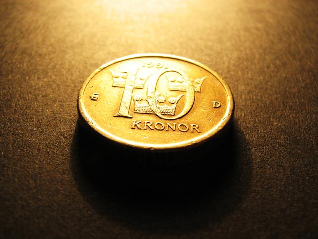 jedna velká zlatá mince osvětlena zezhora